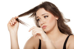 Damaged hair. Dissapointed young woman looking at the ends of her hair Royalty Free Stock Photo