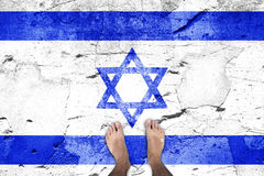 Damaged Israel flag with barefoot man. Top view of a barefoot man stands on damaged cracked cement floor painted with Israel flag. Point of view perspective used Stock Image