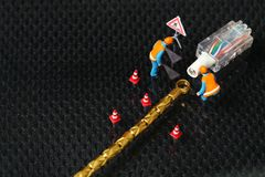 Damaged lan cable scene. The damaged lan connection cable plug and maintenance figure miniature model represent the computor business and technology concept Royalty Free Stock Images