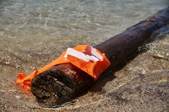 A damaged life jacket. On a log floats on the seashore royalty free stock photos