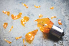 Damaged Light Bulb and Glass Shards. Automotive light bulb in broken condition and sharp glass shards scattered around it on textured background stock image
