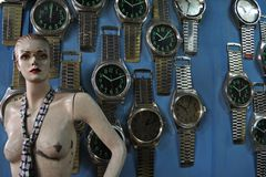 Damaged mannequin of a woman next to large watches on a blue wall stock photos