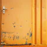 Damaged metal door. Details of damaged door exposing metal under orange paint Royalty Free Stock Photography