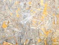 Damaged Oriented Strand Board. Wooden panel made from pressed sandy brown wood shavings as background closeup Stock Photography