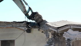Damaged Property bulldozer in action and destroying a house Stock Photo