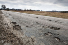 Damaged road. Badly damaged country asphalt road after winter Stock Photography