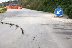 Damaged road with big cracks. Washed out and damaged road with blue traffic sign pointing direction to attract attention Stock Image