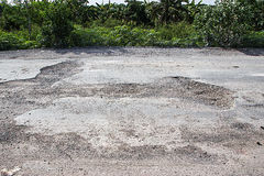 Damaged road in the countryside. Damaged asphalt road with potholes caused, Poor road Royalty Free Stock Photo