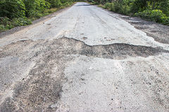 Damaged road in the countryside Stock Photo