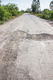 Damaged road in the countryside. Damaged asphalt road with potholes caused, Poor road Royalty Free Stock Photography