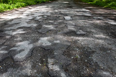 Damaged road full of cracked potholes Royalty Free Stock Photos