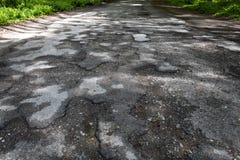 Damaged road full of cracked potholes Royalty Free Stock Photos