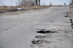 Damaged road. Full of cracks and holes Royalty Free Stock Photo