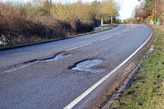 Damaged road with pot holes in it. A highway with deep pot holes caused by traffic wear. Road not being repaired because of austerity Royalty Free Stock Photography