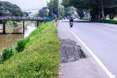 Damaged road with potholes near canal in counreyside Stock Image