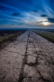 Damaged road in rural countyside with beautifull sunset Stock Image