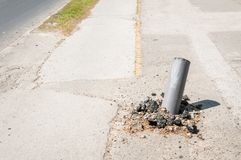 Damaged road traffic barrier metal safety pole hit by fast car in accident and distorted.  Royalty Free Stock Images
