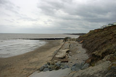 Damaged sea defences. A promenade and sea defences crumbling and falling on to the beach below. Showing erosion on the east coast of England. Background of the Stock Image