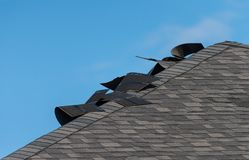 Damaged shingle roof. Damaged ridge section of a roof with curled up asphalt shingles stock photo
