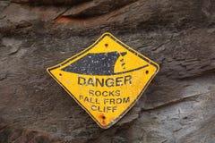 Damaged sign-board falling rocks Royalty Free Stock Photography