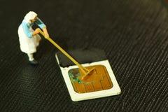 Old simcard scene. Damaged sim card and farmer model scene Stock Photo