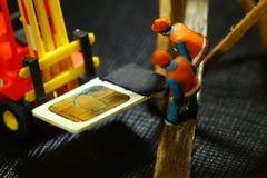 Old simcard scene. Damaged sim card and farmer model scene Royalty Free Stock Photography