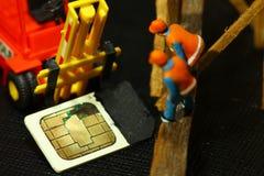 Old simcard scene. Damaged sim card and farmer model scene Royalty Free Stock Image