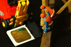 Old simcard scene. Damaged sim card and miniature figure model scene Royalty Free Stock Photography