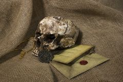 Damaged skull with a letter, with a burlap background. Damaged skull with a vintage letter, with a burlap background royalty free stock photography