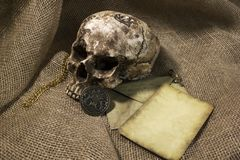 Damaged skull with a letter, with a burlap background. Damaged skull with a vintage letter, with a burlap background royalty free stock image