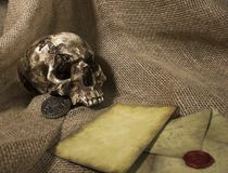 Damaged skull with a letter, with a burlap background. Damaged skull with a vintage letter, with a burlap background stock images