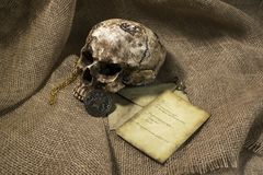 Damaged skull with a letter, with a burlap background. Damaged skull with a vintage letter, with a burlap background stock image