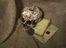 Damaged skull with a letter, with a burlap background. Damaged skull with a vintage letter, with a burlap background stock photo