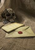 Damaged skull with a letter, with a burlap background. Damaged skull with a vintage letter, with a burlap background royalty free stock images