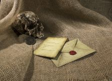 Damaged skull with a letter, with a burlap background. Damaged skull with a vintage letter, with a burlap background royalty free stock photos