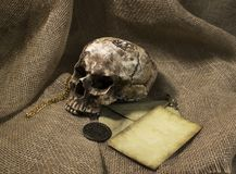 Damaged skull with a letter, with a burlap background stock photo