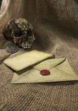 Damaged skull with a letter, with a burlap background. Damaged skull with a vintage letter, with a burlap background stock photography