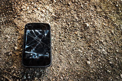Damaged. Smartphone on dirty floor royalty free stock image
