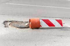 Damaged street reconstruction or construction barricade caution red and white sign cover the open hole of manhole on the road as a Royalty Free Stock Image