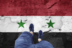 Damaged Syria flag with a man legs. Top view of a man standing on damaged cracked cement floor painted with Syria flag. Point of view perspective used Stock Images