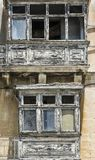 Damaged traditional maltese balcony. Building with traditional maltese balcony in historical part of Valletta. Damaged windows on the facade of a abandoned house Royalty Free Stock Photos
