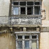 Damaged traditional maltese balcony. Building with traditional maltese balcony in historical part of Valletta. Damaged windows on the facade of a abandoned house Stock Image