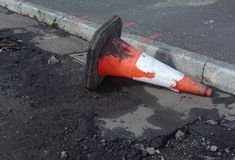 Damaged traffic cone in gutter, road undergoing repairs Stock Photo