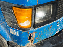 Damaged Truck. Damaged blue truck detail, rusted through front fender, broken turn indicator light Royalty Free Stock Photography