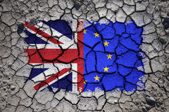 Damaged Uk and Eu flags on cracked soil Royalty Free Stock Photos