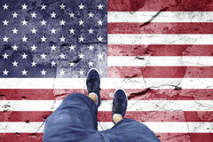 Damaged Usa flag with a man. Top view of a man standing on damaged cracked cement floor painted with Usa flag. Point of view perspective used. Conceptual United Stock Photos