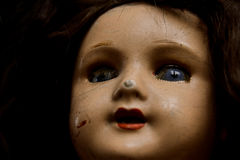 Damaged Vintage Doll. Closeup of an old damaged doll. Shallow Depth of Field, focus on the eyes. High contrast stock image