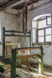 Damaged vintage weaving machine in an old abandoned house with grunge wall and wooden ceiling. Royalty Free Stock Photography