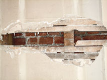 Damaged wall. Damaged plaster on the room wall with exposed brick as a background royalty free stock photos