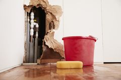 Free Damaged Wall, Exposed Burst Water Pipes, Sponge And Bucket Stock Photo - 104864210